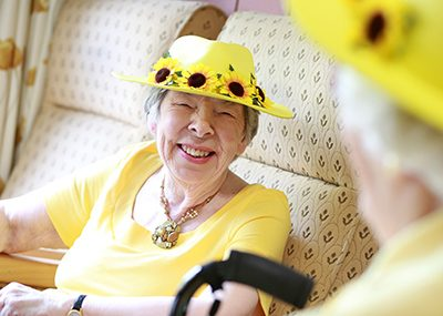 Older woman, laughing, wearing a hat covered in sunflowers.
