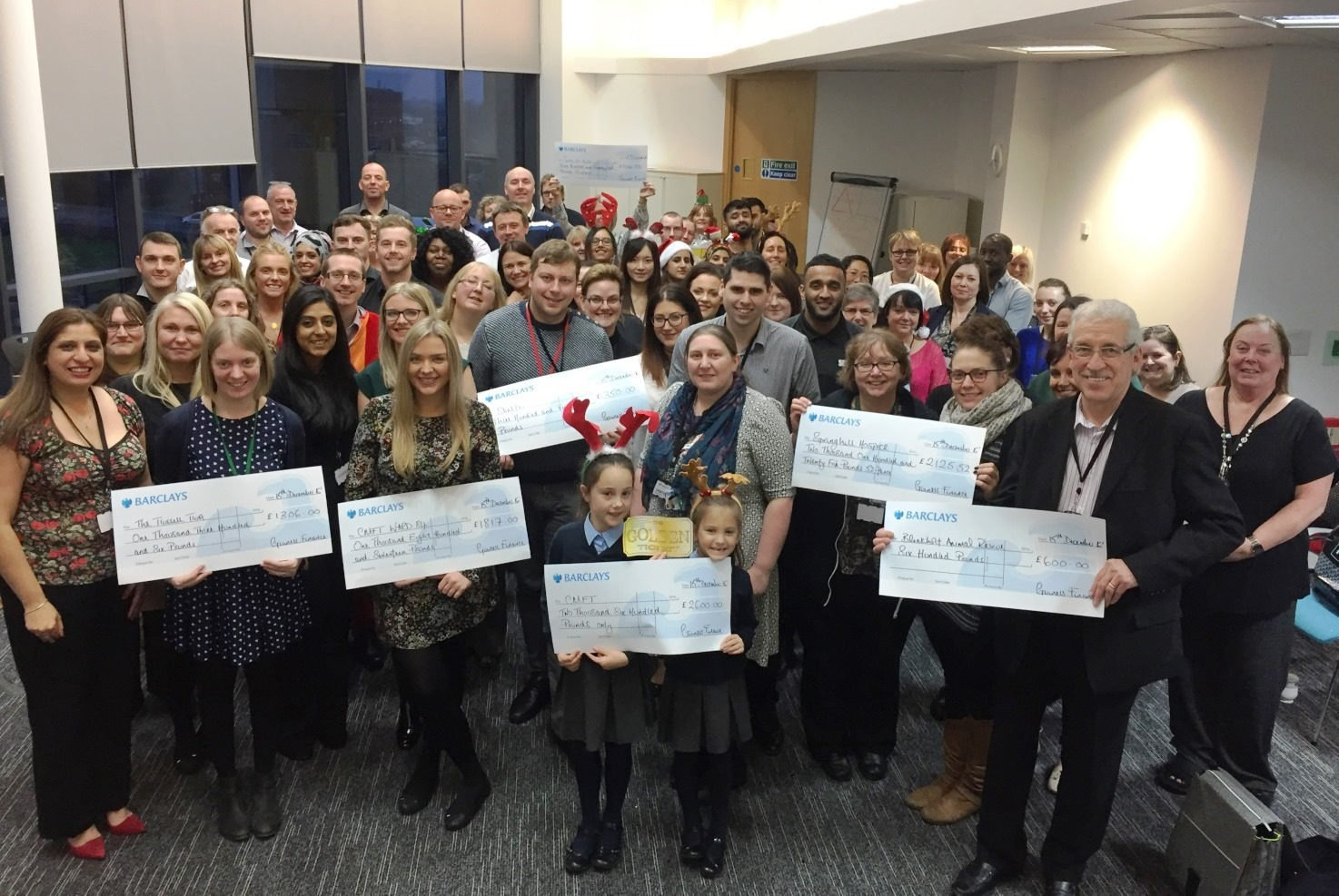 Finance staff, charity reps and their cheques.