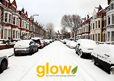 Road of a terraced street showing cars and houses covered with a blanket of snow. The Glow logo is positioned at the bottom.