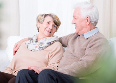 An older couple sitting on their sofa having a chat.